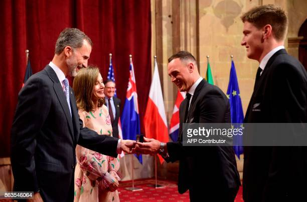 Spain's King Felipe VI and Queen Letizia give a medal to 'All Blacks' New Zealand national rugby union team players Israel Dagg and Jordie Barrett...
