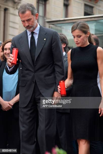 Spain's King Felipe VI and Spain's Queen Letizia hold a candle for the victims of the Barcelona attack on Las Ramblas boulevard in Barcelona on...