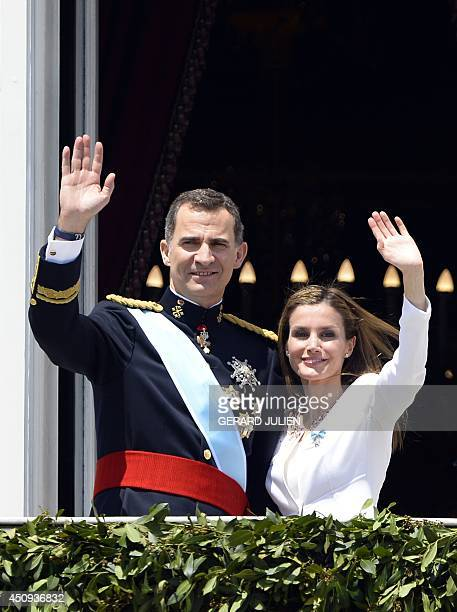 Spain's King Felipe VI and Spain's Queen Letizia wave from the balcony of the Palacio de Oriente or Royal Palace in Madrid on June 19 2014 following...