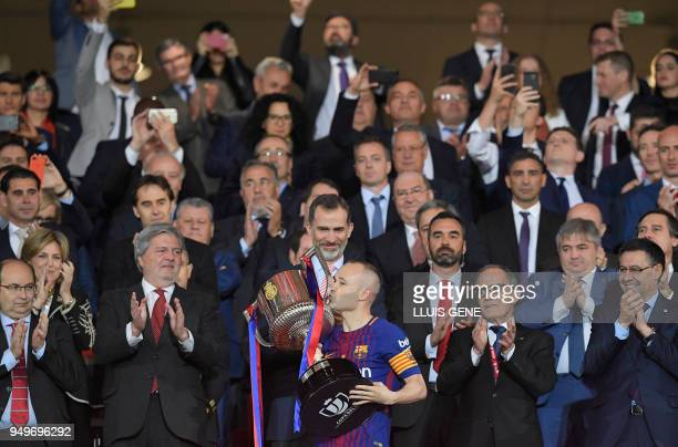 TOPSHOT Spain's king Felipe VI handles the trophy to Barcelona's Spanish midfielder Andres Iniesta after the Spanish Copa del Rey final football...