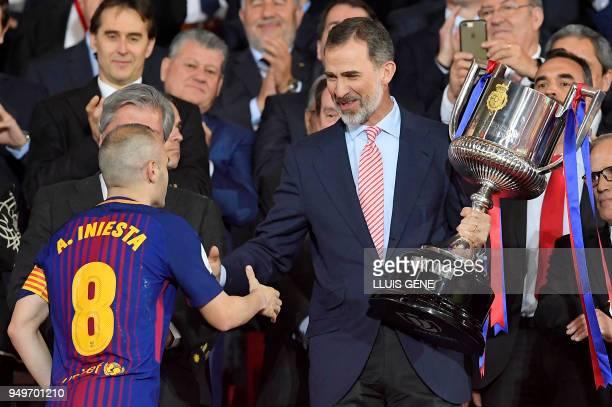 TOPSHOT Spain's king Felipe VI handles the trophy to Barcelona's Spanish midfielder Andres Iniesta after the Spanish Copa del Rey final football...
