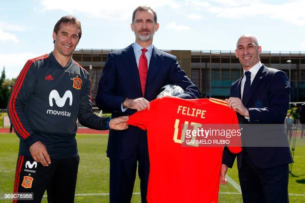 Spain's king Felipe VI holds a football jersey with his name as he poses with Spanish Royal Footbal Federation president Luis Manuel Rubiales and...