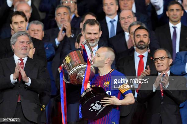 Spain's king Felipe VI looks at Barcelona's Spanish midfielder Andres Iniesta kissing the trophy after the Spanish Copa del Rey final football match...
