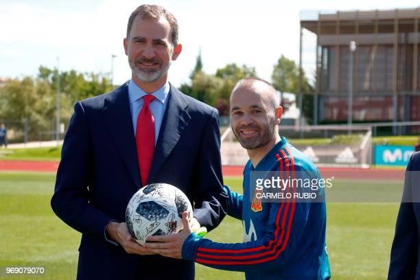 Spain's king Felipe VI poses with Spain's midfielder Andres Iniesta during his visit to the Spain's national football team at Las Rozas de Madrid...