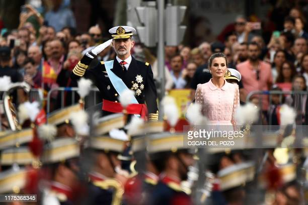 Spain´s King Felipe VI salutes soldiers next to Queen Letizia during the Spanish National Day military parade in Madrid on October 12, 2019.