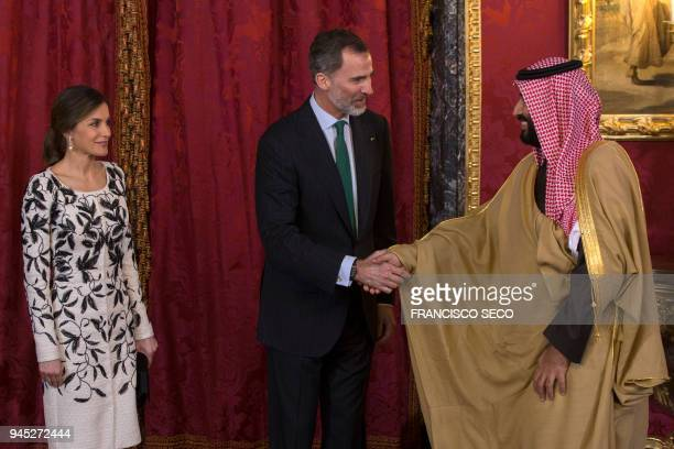 Spain's king Felipe VI shakes hands with Saudi crown prince Mohammed bin Salman beside queen Letizia before a lunch at the Royal Palace in Madrid on...