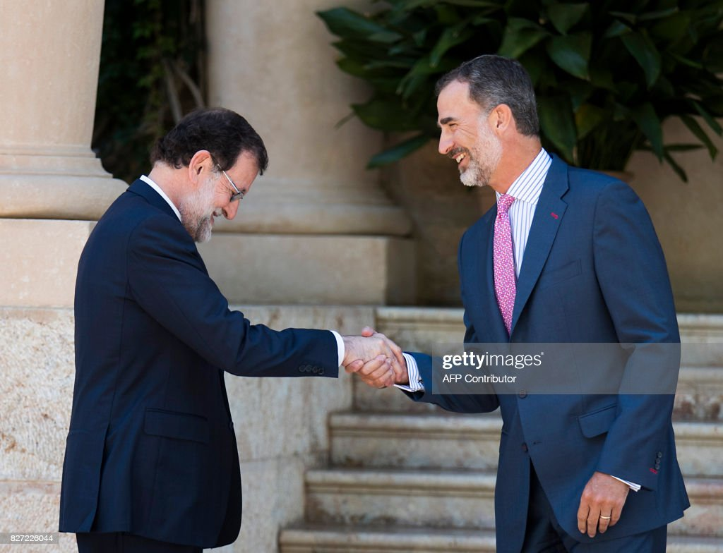 Spain's King Felipe VI (R) shakes hands with Spanish Prime Minister Mariano Rajoy before their meeting at the Marivent Palace in Palma de Mallorca on August 7, 2017. The royal family traditionally spends its summer holidays at the Marivent Palace. /
