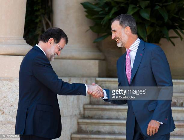 Spain's King Felipe VI shakes hands with Spanish Prime Minister Mariano Rajoy before their meeting at the Marivent Palace in Palma de Mallorca on...