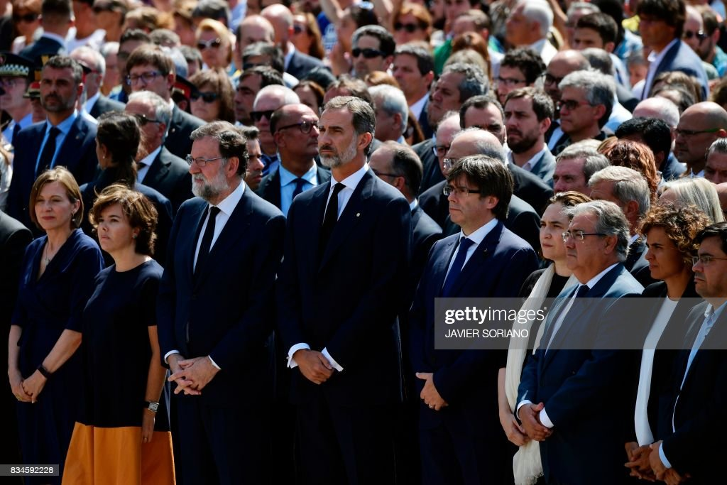 TOPSHOT - Spain's King Felipe VI (4thL), Spanish Prime Minister Mariano Rajoy (3rdL), President of Catalonia Carles Puigdemont (5thR), Spanish vice-President of the Government and Minister of the Presidency and of the Regional Administrations Soraya Saenz de Santamaria (2ndL), Barcelona's mayor Ada Colau (4thR), President of the Catalan parliament Carme Forcadell (L) and officials observe a minute of silence for the victims of the Barcelona attack at Plaza de Catalunya on August 18, 2017, a day after a van ploughed into the crowd, killing 13 persons and injuring over 100 on the Rambla in Barcelona. Drivers have ploughed on August 17, 2017 into pedestrians in two quick-succession, separate attacks in Barcelona and another popular Spanish seaside city, leaving 13 people dead and injuring more than 100 others. In the first incident, which was claimed by the Islamic State group, a white van sped into a street packed full of tourists in central Barcelona on Thursday afternoon, knocking people out of the way and killing 13 in a scene of chaos and horror. Some eight hours later in Cambrils, a city 120 kilometres south of Barcelona, an Audi A3 car rammed into pedestrians, injuring six civilians -- one of them critical -- and a police officer, authorities said. /