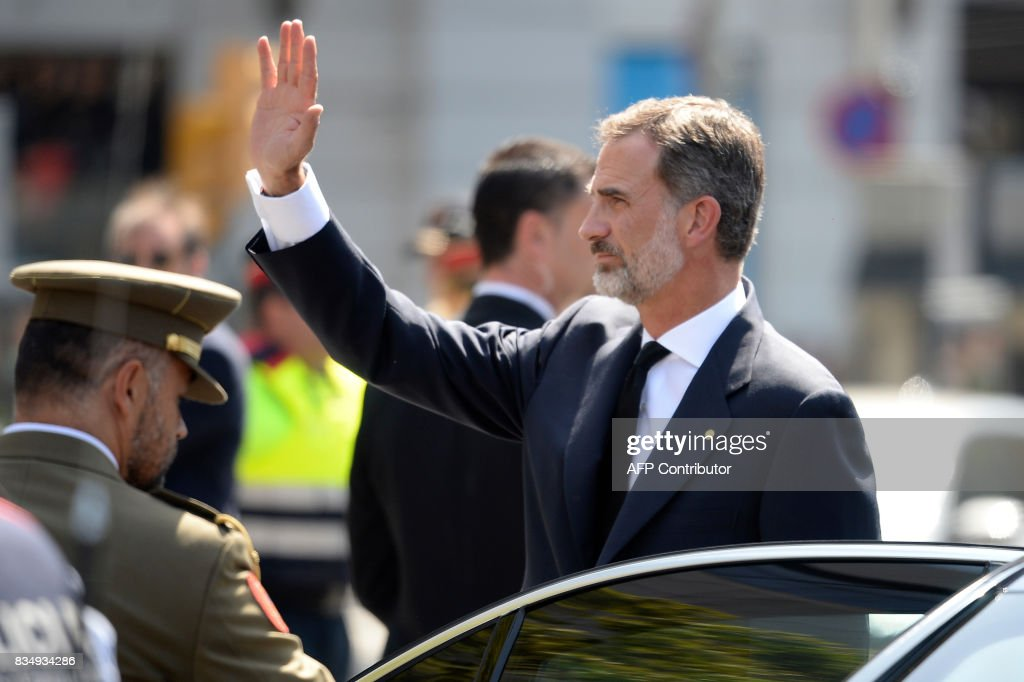 Spain's King Felipe VI waves as he arrives prior to observing a minute of silence for the victims of the Barcelona attack at Plaza de Catalunya on August 18, 2017, a day after a van ploughed into the crowd, killing 13 persons and injuring over 100 on the Rambla in Barcelona. Drivers have ploughed on August 17, 2017 into pedestrians in two quick-succession, separate attacks in Barcelona and another popular Spanish seaside city, leaving 13 people dead and injuring more than 100 others. In the first incident, which was claimed by the Islamic State group, a white van sped into a street packed full of tourists in central Barcelona on Thursday afternoon, knocking people out of the way and killing 13 in a scene of chaos and horror. Some eight hours later in Cambrils, a city 120 kilometres south of Barcelona, an Audi A3 car rammed into pedestrians, injuring six civilians -- one of them critical -- and a police officer, authorities said. / AFP PHOTO / Josep LAGO