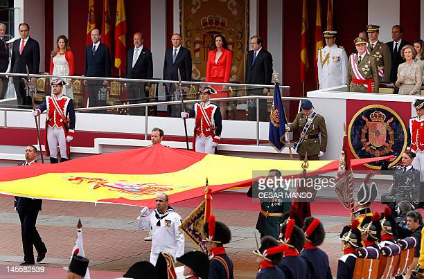 Spain's King Juan Carlos and Queen Sofia pay their respects to the Spanish flag during a military parade marking the Armed Forces Day on June 2, 2012...