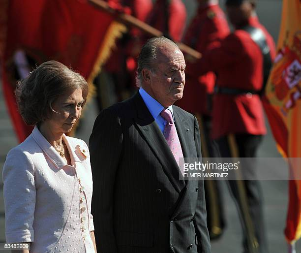 Spain's King Juan Carlos and Queen Sofia review a guard of honor upon their arrival to El Salvador's airport in Comalapa some 45 kms south of San...