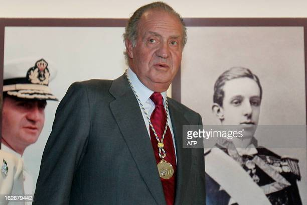 Spain's King Juan Carlos and Sofia pose in front of pictures of the royal family during their visit 22 November 2006 to the Canary Islands in...