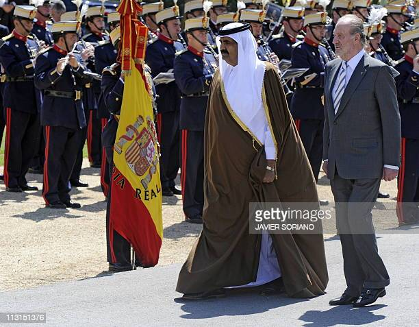Spain's King Juan Carlos and the Emir of the State of Qatar Sheikh Hamad bin Khalifa AlThani review the honor guard upon their arrival at El Pardo...