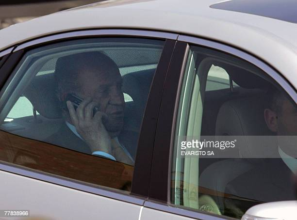 Spain's King Juan Carlos de Borbon talks on his mobile phone while he leaves the Espacio Riesco in Santiago after the morning plenary of the Ibero...