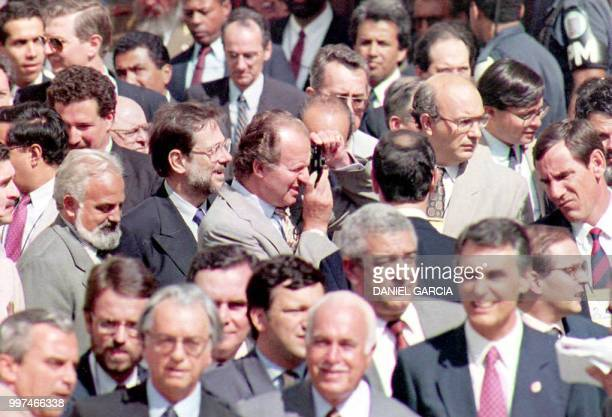 Spain's King Juan Carlos I takes a snapshot 16 July 1993 during a family photo in Salvador de Bahia Brazil's historical district on the last day of...