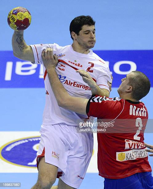 Spain's left back Alberto Entrerrios vies with Serbia's left back Milos Dragas during the 23rd Men's Handball World Championships round of 16 match...