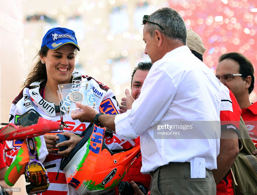Spain's Leila Sanz, first female biker in the final placings, receives a medal from the Director of the Rally dakar Etienne Lavigne on the podium of the 2013 Dakar Rally, in Santiago, Chile on January 20, 2013..