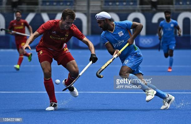 Spain's Llorenc Piera and India's Simranjeet Singh vie for the ball during their men's pool A match of the Tokyo 2020 Olympic Games field hockey...