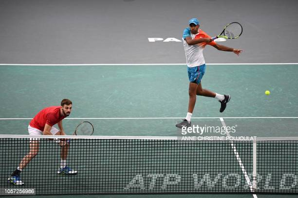 Spain's Marcel Granollers and Rajeev Ram of the US return the ball to Netherlands' JeanJulien Rojer and Romania's Horia Tecau during their men's...