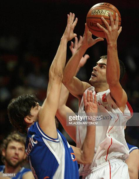 Spain's Massimo Bulleri goes for a basket as Italy's Roberto Chiacig tries to block him 13 September 2003 during the semifinals of the mens FIBA 2003...