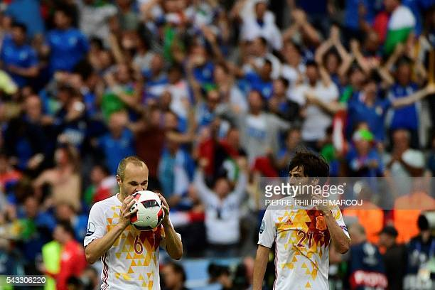 TOPSHOT Spain's midfielder Andres Iniesta and Spain's midfielder David Silva react after the Euro 2016 round of 16 football match between Italy and...