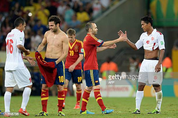 Spain's midfielder Andres Iniesta and Tahiti's midfielder Jonathan Tehau greet each other as Spain's midfielder Cesc Fabregas and Tahiti's midfielder...