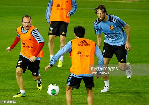 Spain's midfielder Andres Iniesta controls the ball past Spain's forward Michu during a training session at the Carlos del Monte stadium in Albacete...