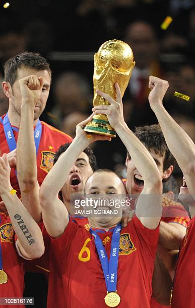 Spain's midfielder Andres Iniesta holds the trophy after the award ceremony following the 2010 FIFA football World Cup between the Netherlands and...
