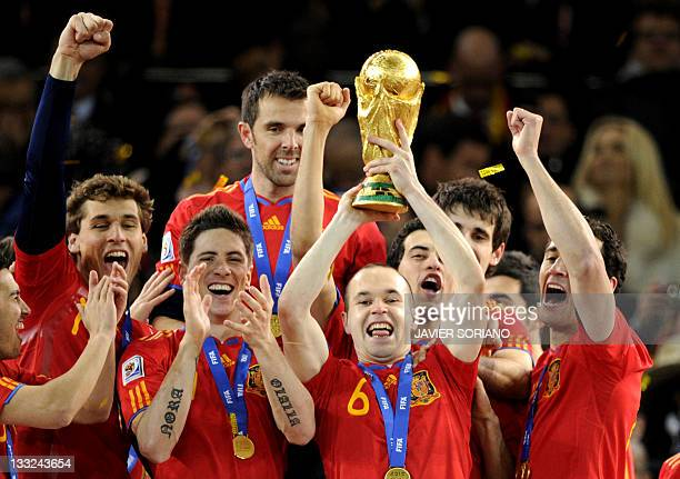 Spain's midfielder Andres Iniesta raises the trophy as Spain's national football team players celebrate winning the 2010 World Cup football final...
