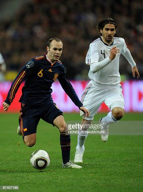 Spain's midfielder Andres Iniesta runs past France's defender Julien Escude during a friendly international football match at the stade de France in...