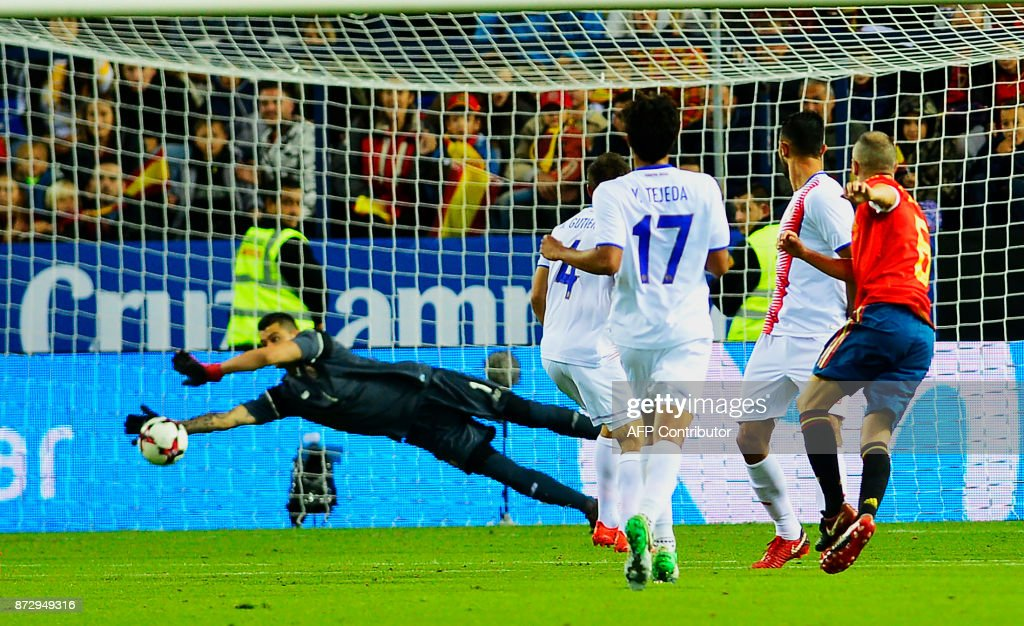 Spain's midfielder Andres Iniesta (R) scores against Costa Rica's goalkeeper Danny Carvajal during the international friendly football match Spain against Costa Rica at La Rosaleda stadium in Malaga on November 11, 2017. /