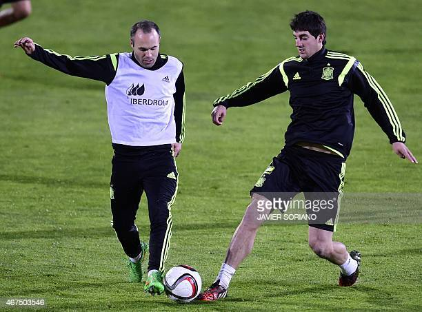Spain's midfielder Andres Iniesta vies with Spain's defender Mikel San Jose during a training session at the Sport City training ground in Las Rozas...