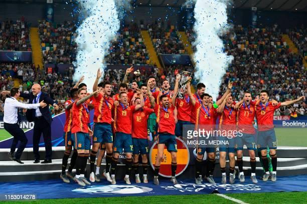 Spain's midfielder Dani Ceballos and Spain's defender Jesus Vallejo (C-R, holding the winners trophy, Spain's head coach Luis de la Fuente and...