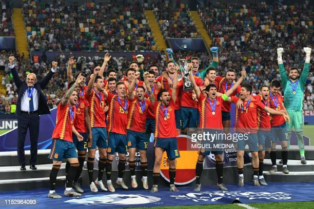 Spain's midfielder Dani Ceballos and Spain's defender Jesus Vallejo holding the winners trophy Spain's head coach Luis de la Fuente and players...
