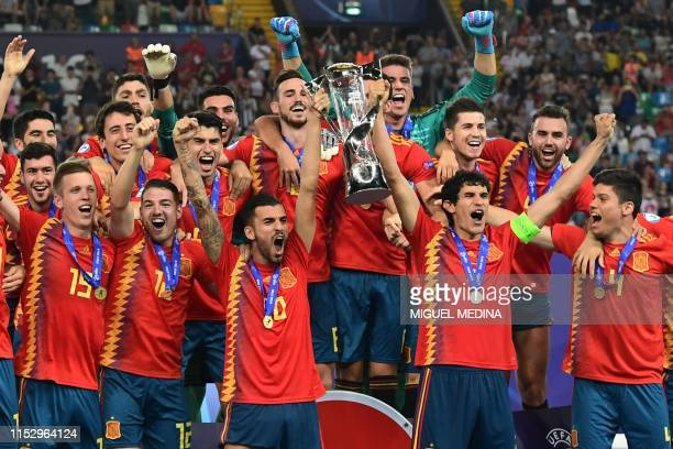 Spain's midfielder Dani Ceballos and Spain's defender Jesus Vallejo , holding the winners trophy, and teammates celebrate after winning the final...