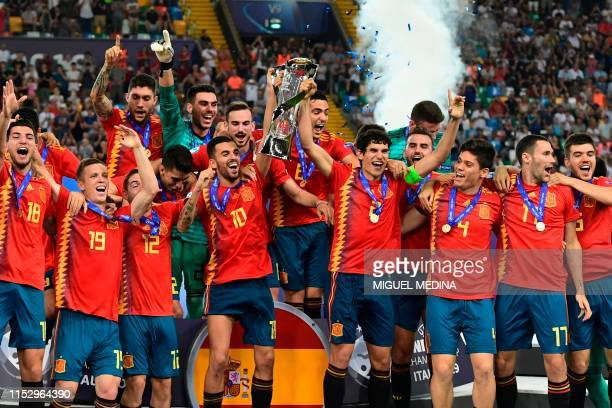 Spain's midfielder Dani Ceballos and Spain's defender Jesus Vallejo hold the winners trophy and celebrate with teammates after Spain won the final...