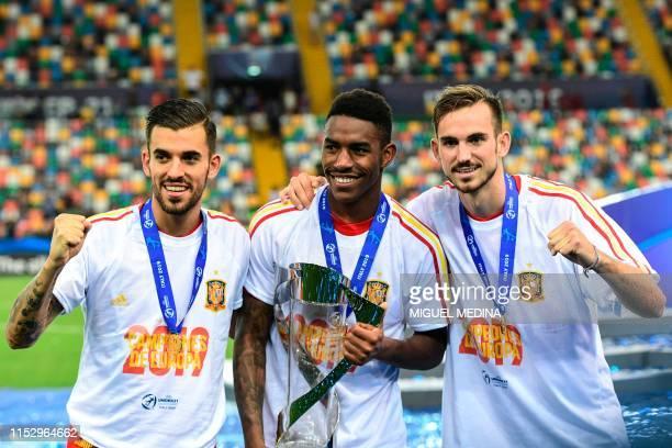 Spain's midfielder Dani Ceballos, Spain's defender Junior Firpo and Spain's midfielder Fabian Ruiz celebrate with the winners' trophy after Spain won...