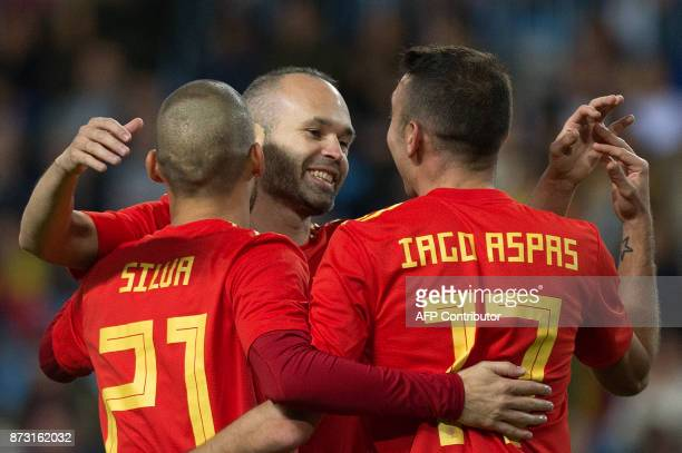 Spain's midfielder David Silva celebrates with midfielder Andres Iniesta and forward Iago Aspas after scoring during the international friendly...