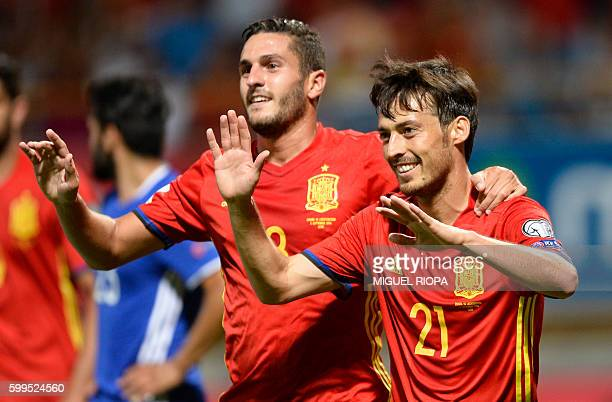 Spain's midfielder David Silva celebrates with teammate midfielder Koke after scoring a goal during the WC 2018 football qualification match between...