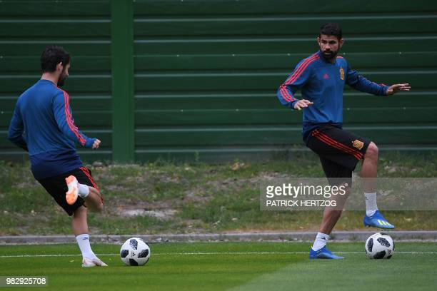 Spain's midfielder Isco and Spain's forward Diego Costa take part in a training session at Mirniy Stadium in Kaliningrad on June 24 2018 on the eve...