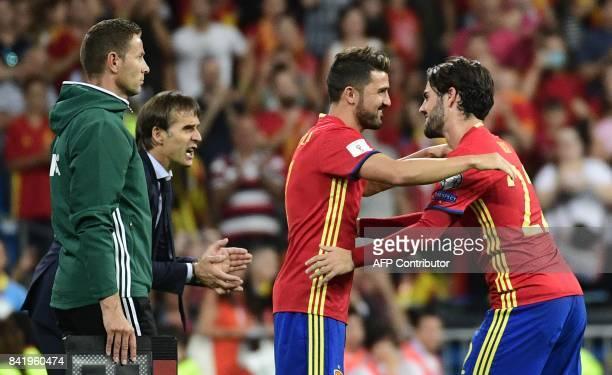 Spain's midfielder Isco cheers teammate Spain's forward David Villa beside Spain's coach Julen Lopetegui before leaving the field during the World...