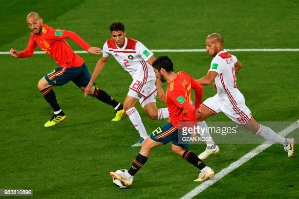Spain's midfielder Isco controls the ball past Spain's forward David Silva Morocco's defender Achraf Hakimi and Morocco's midfielder Karim El Ahmadi...