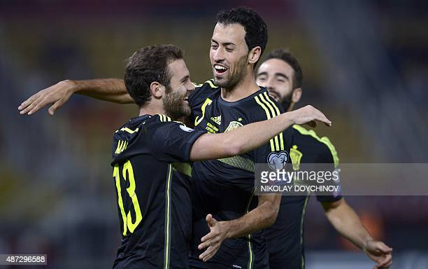 Spain's Midfielder Juan Mata celebrates with his teammate midfielder Sergio Busquets after scoring during the Euro 2016 Group C qualifying football...