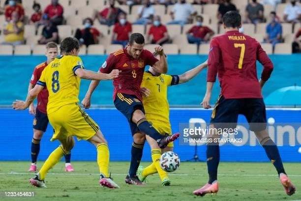 Spain's midfielder Koke attempts a shot on goal as he is marked by Sweden's midfielder Sebastian Larsson and Sweden's midfielder Albin Ekdal during...
