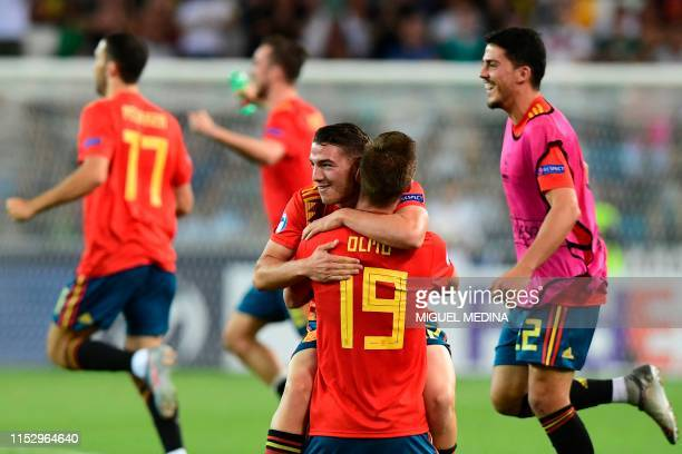 Spain's midfielder Manu Vallejo embraces Spain's forward Dani Olmo as Spain's players celebrate at the end of the final match of the UEFA U21...