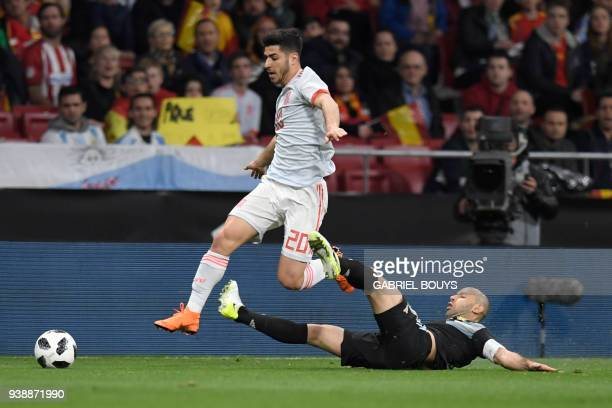Spain's midfielder Marco Asensio jumps over Argentina's defender Javier Mascherano during a friendly football match between Spain and Argentina at...