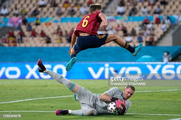 Spain's midfielder Marcos Llorente jumps over Sweden's goalkeeper Robin Olsen during the UEFA EURO 2020 Group E football match between Spain and...