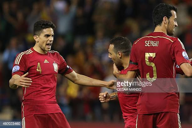 Spain's midfielder Santi Cazorla celebrates with Spain's defender Marc Bartra during the Euro 2016 qualifying football match Spain vs Luxembourg at...