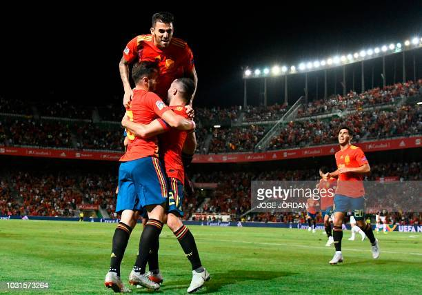 Spain's midfielder Saul Niguez celebrates with Spain's defender Dani Carvajal and Spain's midfielder Dani Ceballos after scoring a goal during the...